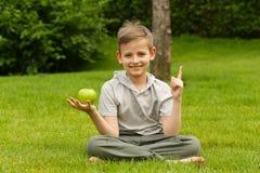 Un muchacho en un parque debajo de un árbol con una manzana Foto de archivo