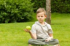 Un muchacho en un parque debajo de un árbol con una manzana Foto de archivo libre de regalías