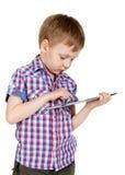Un muchacho en una camisa de tela escocesa con un ordenador de la tablilla Imagen de archivo