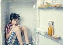 Un muchacho en una camisa y pantalones cortos que come una barra de chocolate dentro de un refrigerador abierto con la comida Fotografía de archivo