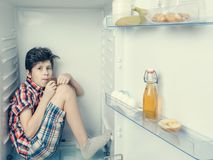 Un muchacho en una camisa y pantalones cortos que come una barra de chocolate dentro de un refrigerador abierto con la comida Foto de archivo libre de regalías