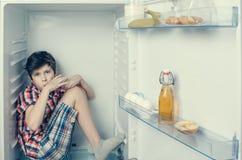 Un muchacho en una camisa y pantalones cortos que come una barra de chocolate dentro de un refrigerador con la comida y el produc Foto de archivo