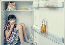 Un muchacho en una camisa y pantalones cortos que come una manzana dentro de un refrigerador con la comida y el producto Fotografía de archivo libre de regalías