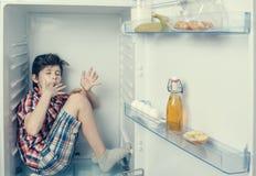 Un muchacho en una camisa y pantalones cortos que lame un los fingeres del ` s dentro de un refrigerador abierto con la comida pe Imagen de archivo libre de regalías