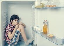 Un muchacho en una camisa y pantalones cortos que lame un los fingeres del ` s dentro de un refrigerador abierto con la comida pe Fotos de archivo