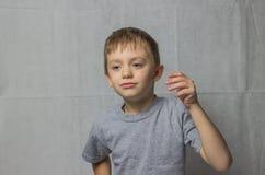 Un muchacho en una camiseta gris en sensaciones trastornadas no entiende qué está sucediendo fotografía de archivo