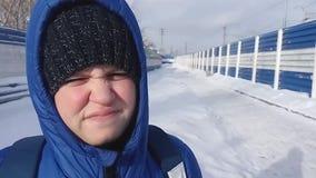 Un muchacho en una chaqueta del invierno, un sombrero y una capilla se está colocando en la calle Slowmo almacen de metraje de vídeo