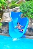 Un muchacho en una diapositiva de agua Imagenes de archivo
