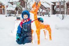 Un muchacho en una yarda del pueblo del invierno adornada para la Navidad Imagenes de archivo