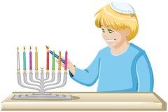 Un muchacho enciende una vela de Hanukkiah