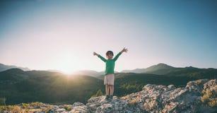 Un muchacho encima de una montaña Imagen de archivo libre de regalías