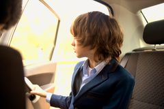 Un muchacho es un adolescente con un pelo largo en un traje clásico en el coche Imagen de archivo libre de regalías