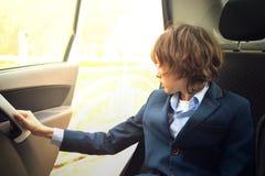 Un muchacho es un adolescente con un pelo largo en un traje clásico en el coche Fotos de archivo