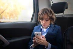 Un muchacho es un adolescente con un pelo largo en un traje clásico en el coche Imágenes de archivo libres de regalías