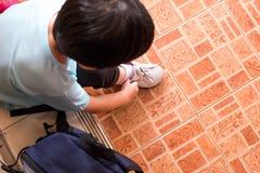 Un muchacho está atando los cordones para prepararse para ir a la escuela en el m Imagen de archivo