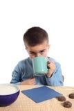 Un muchacho está bebiendo de una taza Imagen de archivo