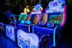 Un muchacho está jugando al videojuego en un centro de juego con los gabinetes coloridos del juego en los grandes almacenes foto de archivo