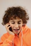 Un muchacho está jugando con su teléfono Fotos de archivo libres de regalías