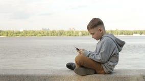 Un muchacho está jugando en una tableta cerca del mar almacen de video