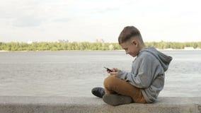 Un muchacho está jugando en una tableta cerca del mar almacen de metraje de vídeo