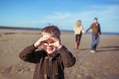 Un muchacho está llevando a cabo las manos como una máscara y sus padres que vienen Imagen de archivo