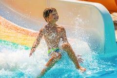 Un muchacho feliz en el tobogán acuático en una piscina que se divierte durante vacaciones de verano en aguamarina hermosa parque foto de archivo