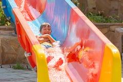 Un muchacho feliz en el tobogán acuático en una piscina que se divierte durante vacaciones de verano en aguamarina hermosa parque fotografía de archivo