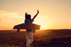 Un muchacho feliz en un traje del super héroe está jugando con un aeroplano a Foto de archivo libre de regalías