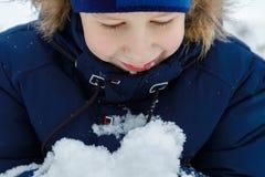 Un muchacho feliz, sonriente está mirando el montón de la nieve en su mano que disfruta del pasatiempo al aire libre del invierno fotografía de archivo libre de regalías