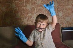 Un muchacho fuertemente emocional en guantes médicos azules muestra una diversa cara en la cámara Imágenes de archivo libres de regalías