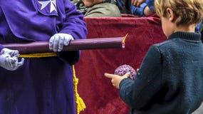 Un muchacho hace una bola de la cera, goteando de una vela en una procesión de la semana santa en Huelva, España fotos de archivo