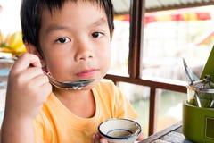 Un muchacho hambriento se está sentando en la tabla de madera para come el postre en r Imágenes de archivo libres de regalías