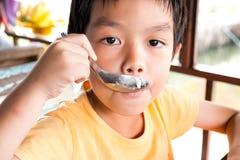 Un muchacho hambriento se está sentando en la tabla de madera para come el postre en r Fotos de archivo