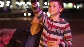 Un muchacho hermoso con su papá que sonríe y que hace a almacen de metraje de vídeo