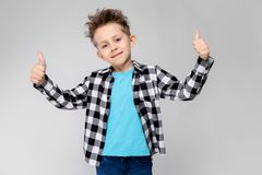 Un muchacho hermoso en una camisa de tela escocesa, camisa azul y vaqueros se coloca en un fondo gris El muchacho sonríe y muestr Foto de archivo libre de regalías