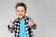 Un muchacho hermoso en una camisa de tela escocesa, camisa azul y vaqueros se coloca en un fondo gris El muchacho sonríe y muestr Fotografía de archivo
