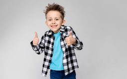 Un muchacho hermoso en una camisa de tela escocesa, camisa azul y vaqueros se coloca en un fondo gris El muchacho sonríe y muestr Imagenes de archivo