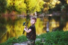 Un muchacho hermoso que sostiene una caña de pescar Fotografía de archivo