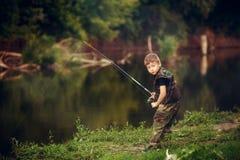 Un muchacho hermoso que sostiene una caña de pescar Imagen de archivo libre de regalías