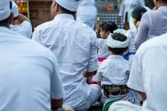 Un muchacho hindú que ruega con su familia Imagen de archivo libre de regalías