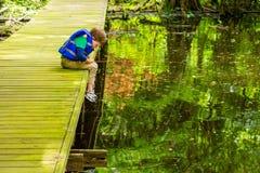 Un muchacho impaciente de la pesca mira fijamente su Bobber inmóvil mientras que él se inclina fotografía de archivo