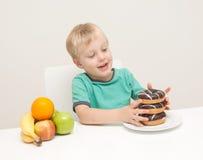 Un muchacho joven considera si él comerá un buñuelo malsano Imagenes de archivo