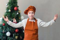 Un muchacho joven de la sonrisa linda en la forma anaranjada de un cocinero aumentó sus manos que invitaban todo el mundo a la ta imágenes de archivo libres de regalías