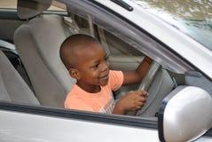 Un muchacho joven emocionado que consigue la sensación de cómo es conducir Imagenes de archivo