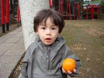 Un muchacho joven en impermeable con una naranja en su mano Fotos de archivo