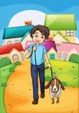 Un muchacho joven feliz que camina con su animal doméstico Foto de archivo