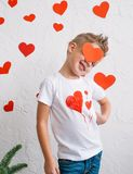 Un muchacho joven lindo en amor con un corazón rojo en su cara Foto de archivo