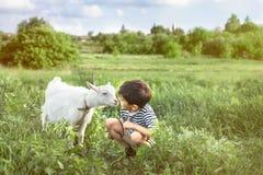 Un muchacho joven que lleva posiciones en cuclillas peladas del chaleco y las negociaciones a una cabra blanca en un césped en un imágenes de archivo libres de regalías