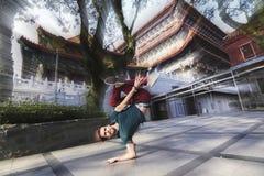 Un muchacho joven que se coloca en una mano en un fondo del templo chino Imagenes de archivo