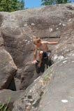 Un muchacho joven que sube y que explora entre una montaña de rocas Foto de archivo libre de regalías
